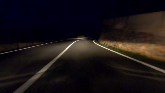132/5000video of a car ride at night on a mountain road with close-up on the asphalt of the road - strada tortuosa video stock e b–roll