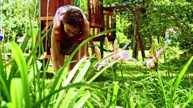 chica adolescente de 15 años de jardinería en el patio, cortar las hierbas en la cama de flor - vídeo