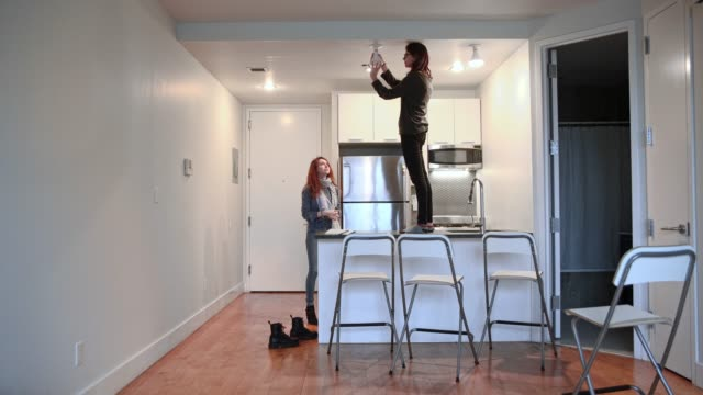 16-years-old teenager girl changing the lighting bulb in the kitchen of the newly rented apartment, and her older sister helps. video