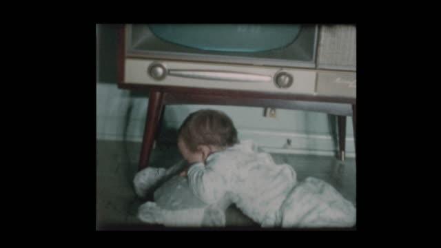 1950s cute little boy checks out vintage antique television set - hotel reception filmów i materiałów b-roll