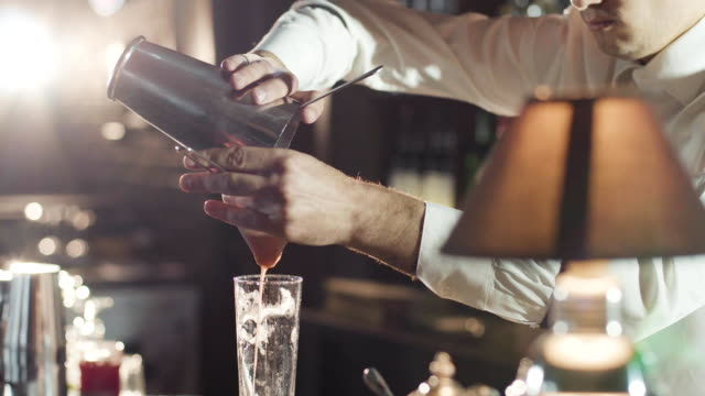 20s bartender in a hat is pouring mixed cocktail from shaker in a glass - alchol video stock e b–roll