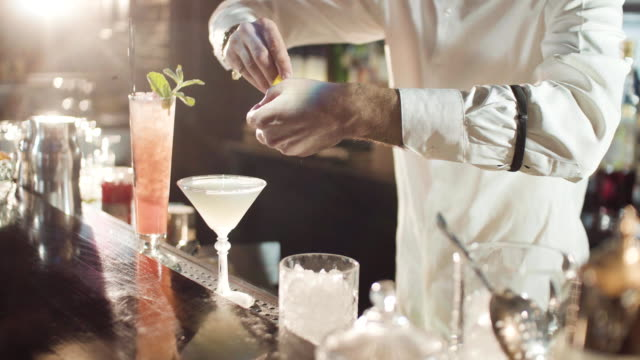 20s bartender is preparing cocktail in a night bar - bartender stock videos and b-roll footage