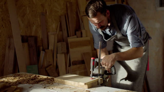 20s bearded woodworker works with brashing machine at sunny day in workshop video