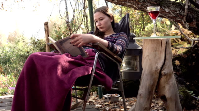 20s girl is reading a book sitting in a rocking chair covered in a blanket outside 4k. video