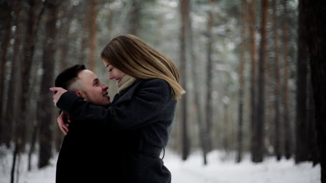 20s Man is lifting his girlfriend and having a fun in a snow winter forest video