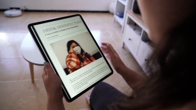 vidéos et rushes de 4k 24fps vidéo d'une fille brune lisant de fausses nouvelles liées à covid 19 pandémie mondiale d'un journal en ligne sur sa tablette dans son salon tout en étant assis sur une balle en forme verte. - interview