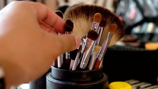 vidéos et rushes de 4k 2shot: main de maquilleur ramasser différentes tailles de brosse de maquillage sur table cosmétique - pinceau à maquillage