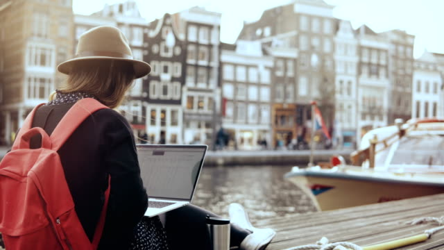 4K 30s happy businesswoman working with laptop. Amsterdam. Lady with red backpack sits on beautiful river embankment 4K 30s happy businesswoman working with laptop. Amsterdam. Lady with red backpack sits on beautiful river embankment. Creative business professional. Mobile office. Wireless internet. Lifestyle shot. amsterdam stock videos & royalty-free footage