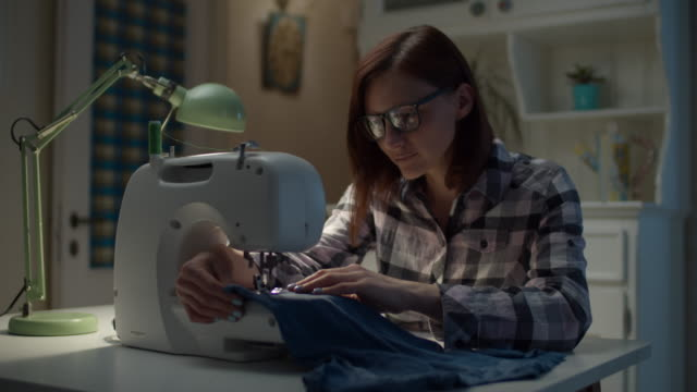 30s woman sewing kids clothes on sewing machine working at home. young mother adjusting sewing machine and sewing t-shirt. - sarta video stock e b–roll