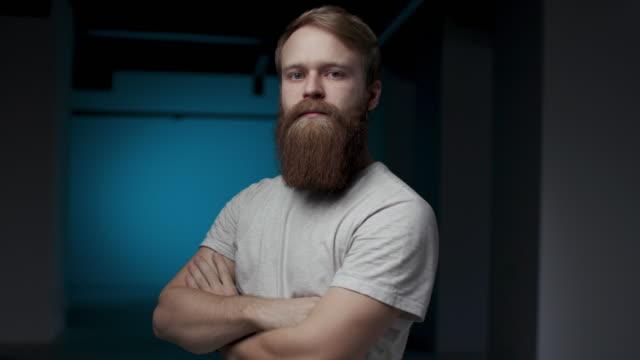 30s ungdomlig man med stort skägg söker nonchalant vänder profil ansikte direkt till kameran. samtida fit male redhead uttryckslös blick concept. säker vuxen entreprenör poserar på middle shot - rött hår bildbanksvideor och videomaterial från bakom kulisserna