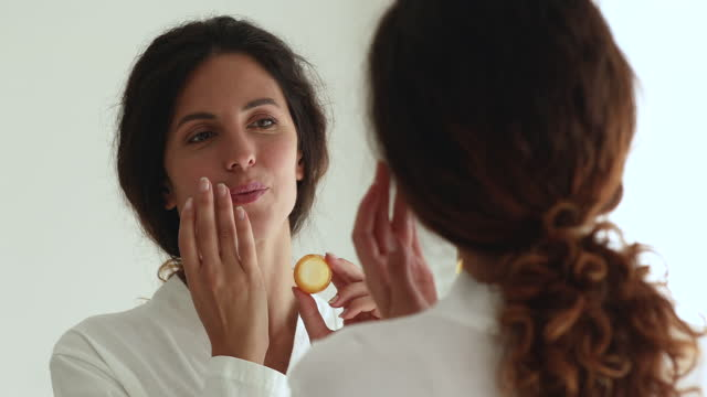 vídeos de stock e filmes b-roll de 35s female look in mirror while applying balm on lips - brilho labial