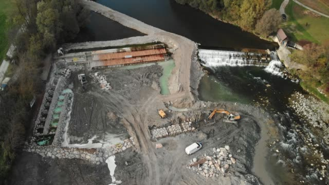 360-degree view of dam construction site in progress Aerial view of dam being reconstructed, shoot with a drone. Constructing a new dam with the help of construction machinery. Digging the pit with excavator. crane construction machinery stock videos & royalty-free footage