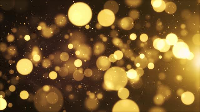 3d gold floating dust bokeh particles in the air con flare su sfondo loop nero in animazione al rallentatore - christmas movie video stock e b–roll