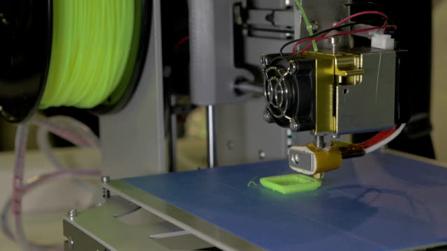 3d printer in process. It makes pieces for equipment with green plastic video