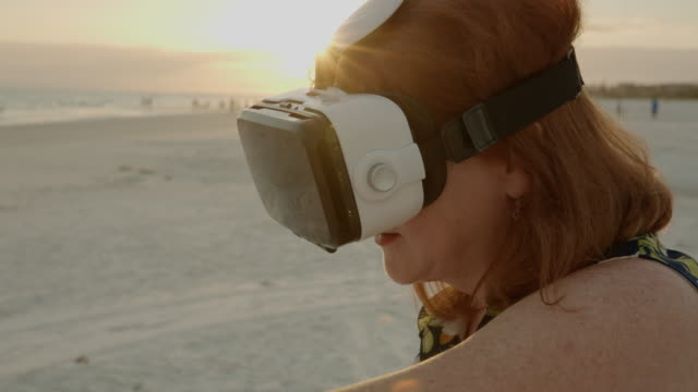 3d virtual reality googles headset sunset florida beach senior woman - google filmów i materiałów b-roll