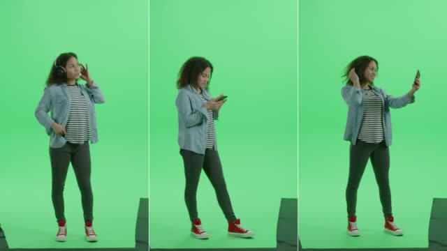 3-in-1 green screen collage: schöne teenage girl verwendet smartphone, trägt kopfhörer, hört musik und tänze, stöbert über internet, social media. multiple angle best value package - blickwinkel der aufnahme stock-videos und b-roll-filmmaterial