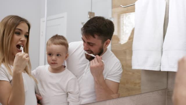 3-Year-Old Boy Watching his Parents Brushing Teeth