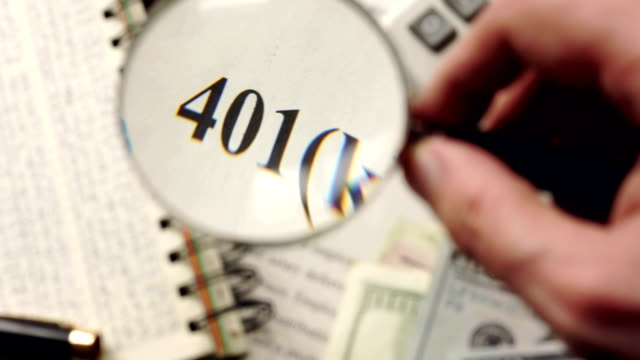 401k plan is watched with magnifier. Retirement concept. Selective focus.