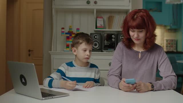 stockvideo's en b-roll-footage met jaren '40 moeder surfen internet op mobiele telefoon en zoon met autisme maken online huiswerk in de buurt. autistic jongen die in notitieboekje dichtbij mamma schrijft gebruikend cel. - lagere schoolleeftijd