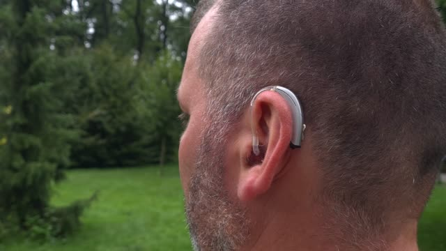 a 40-year-old deaf male wears a technologically advanced hearing aid in his ear - sordità video stock e b–roll