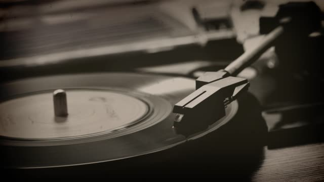 45rpm single record on a turntable. Monochrome.