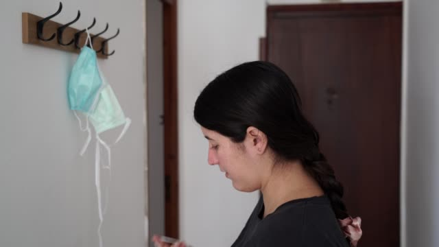 4k 24fps video of a spanish girl taking a surgical mask from a coat rack in fixed on the wall and putting it herself, to afterwards look at camera and smiling giving a positive feeling about pandemic - new normal video stock e b–roll