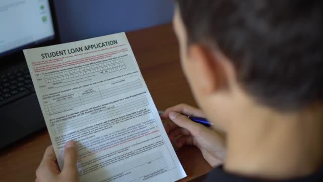 4k. a young man is applying for a student loan - długi filmów i materiałów b-roll