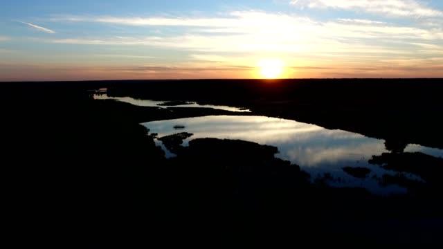 4k aerial - amazing sunset over forest lake. - four seasons filmów i materiałów b-roll