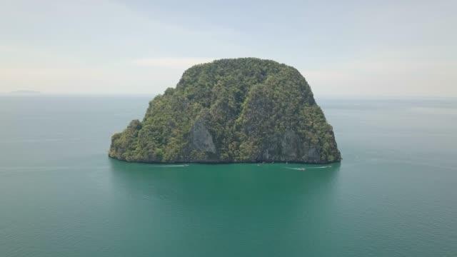 4k aerial of a small thai island with long tail boats and blue sky - four seasons filmów i materiałów b-roll