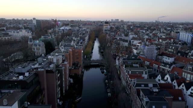 4k antenn skott flyger över kanalerna i amsterdam under solnedgången - drone amsterdam bildbanksvideor och videomaterial från bakom kulisserna