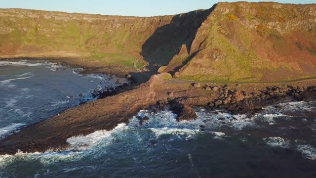 vídeos y material grabado en eventos de stock de tiro aéreo 4k de rocas de la calzada del gigante en irlanda del norte - basalto