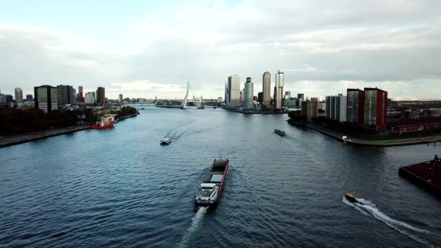 4k aerial shot of ships in rotterdam canal, erasmusbrug bridge and skyscrapers - amsterdam video stock e b–roll