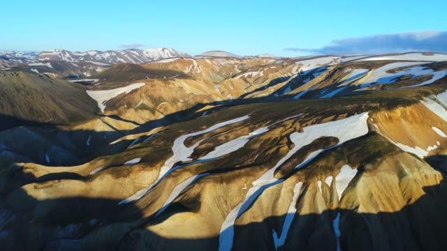 stockvideo's en b-roll-footage met 4 k-luchtfoto van valley nationaalpark landmannalaugar. zijn de velden van de sneeuw en gletsjers op de zachte hellingen van de bergen. prachtige ijsland in de zomer - geologie