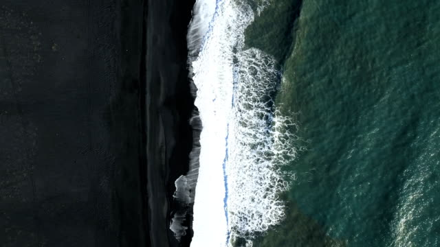 4k aerial video of waves splashing over a black beach video