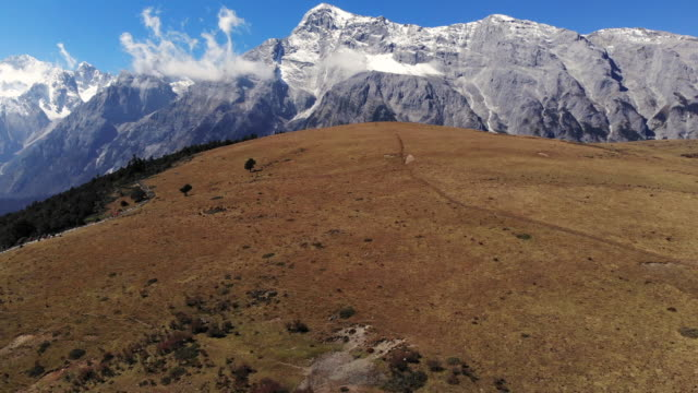 4k Aerial view and dolly back of Field and Jade dragon snow mountain landscape in Lijiang, China.