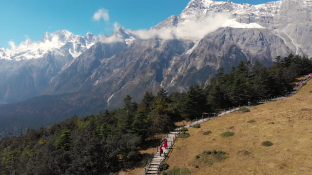 4k Aerial view and dolly forward of Field and Jade dragon snow mountain landscape in Lijiang, China.
