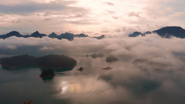 4k aerial view flying above the cloud in morning time at chiaw lan dam in khao sok. - pasmo górskie filmów i materiałów b-roll
