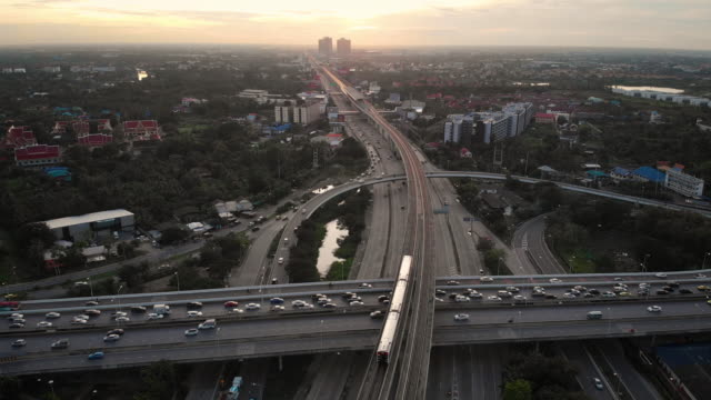 4k aerial view of bts skytrain and city street in sunset time. - наклон вверх стоковые видео и кадры b-roll