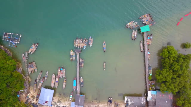 4k aerial view of longtail boat at fishing village in south of Thailand video