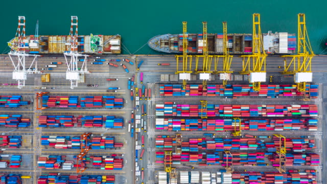 vidéos et rushes de 4k, vaisseau porte-conteneurs timelapse vue aérienne transportant le conteneur dans l'import export export ecitiale et le transport international par porte-conteneurs en haute mer. - doha