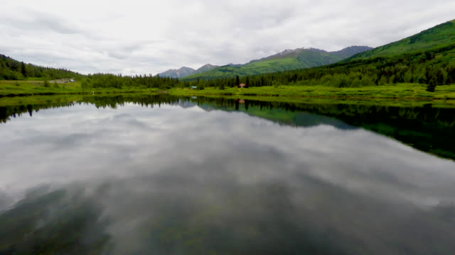 4k Arial drone shot of Alaska mirror glass calm lake in the mountains with puffy white clouds reflecting off the water as the camera tracks toward 2 rustic old mountain cabins on the side of the lake video