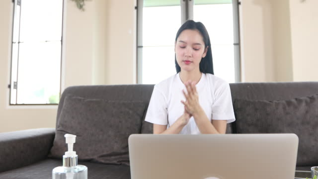 4k Asian Businesswoman working from home and she is Cleaning her hands with sanitizer gel for protective coronavirus. She is quarantined at home during the coronavirus epidemic. video