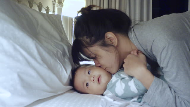 4k : Asian mother lying in bed at home. Thailand video