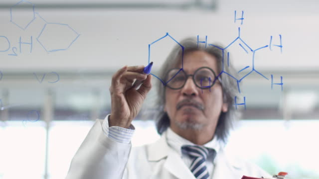 4k: Asian scientist writing chemical formula on glass board.