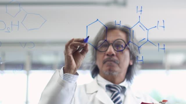 4k: asiatische wissenschaftler schreiben chemische formel auf glasplatte. - wasserstoff stock-videos und b-roll-filmmaterial