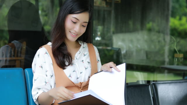 stockvideo's en b-roll-footage met 4 k aziatische vrouwen lezen boek en lachend en gelukkig ontspannend in een koffieshop - woman home magazine