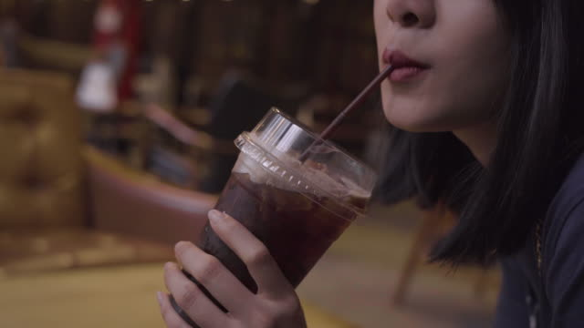 4k Asian young girl having a glass of coffee at the vintage cafe, using straw. breaking her legs during the day with less sugar americano coffee, reduced  stress at cafe, cafe therapy, coffee break coffee shop, drinking iced coffee straw stock videos & royalty-free footage