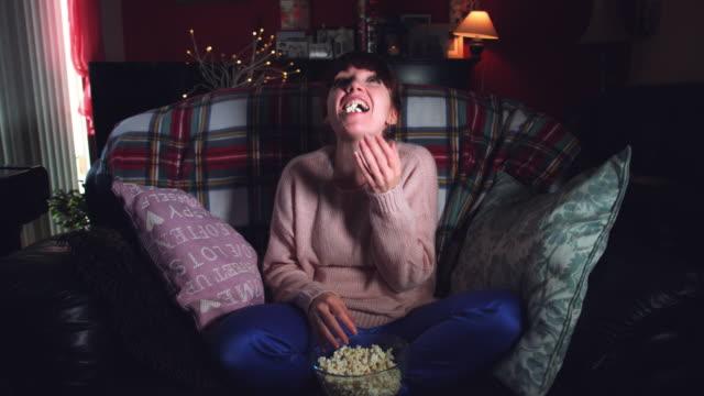 4k scatto autentico di una donna divertente che guarda film comici con popcorn - christmas movie video stock e b–roll