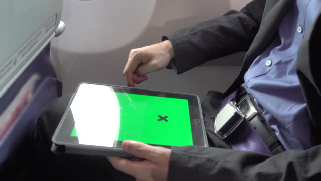 4k: business asian man using tablet on the plane with green screen - surfować po internecie filmów i materiałów b-roll