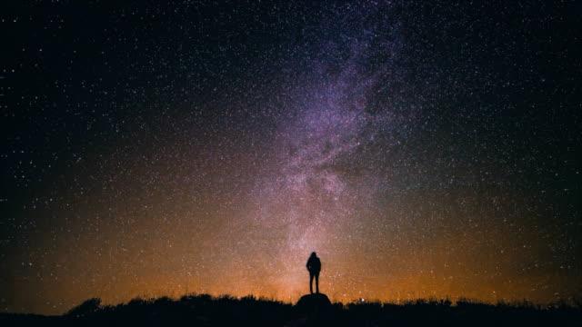 4k Cinemagraph of man star gazing in wonder at night sky